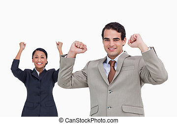 Cheering salesman with colleague behind him against a white ...