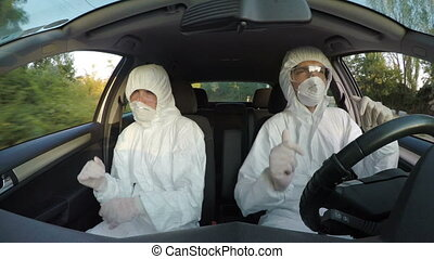 Cheering scientists in hazmat suit dancing and having fun at work in car while driving to contagious field