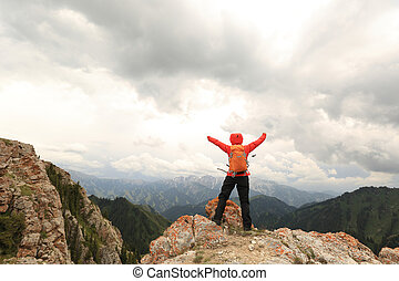 cheering successful woman backpacker open arms on mountain ...