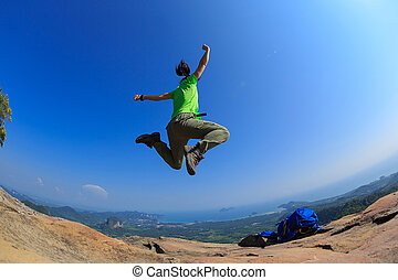 cheering successful young woman hiker jumping on mountain peak