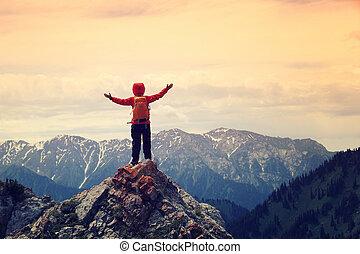 cheering woman hiker open arms on mountainpeak