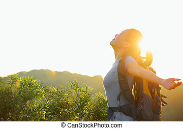 cheering woman hiker open arms to the sunrise stand at ...