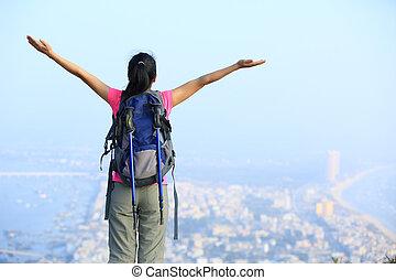 cheering woman hiker seaside mountain peak