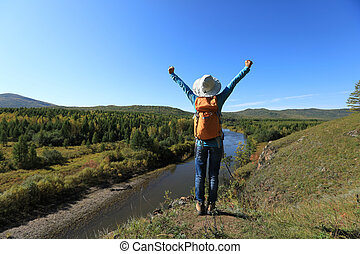 cheering woman hiker with backpack hiking in the autumn forest