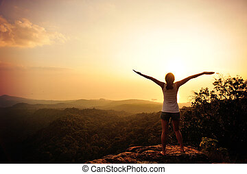 cheering woman open arms at sunset mountain peak
