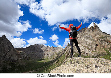 cheering woman with backpack hiking in mountains