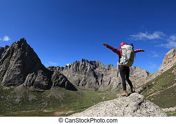 cheering woman with backpack hiking in mountains travel lifestyle success concept