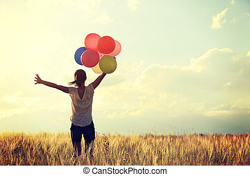cheering young asian woman open arms on grassland with colored balloons