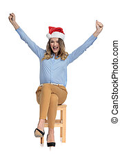 Cheering young businesswoman wearing santa hat