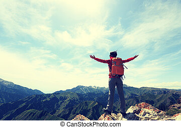 cheering young woman backpacker open arms on mountain peak ...