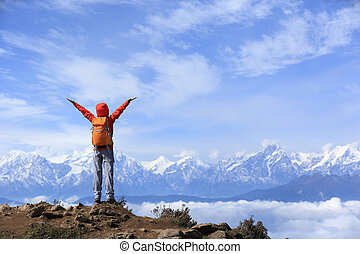 cheering young woman hiker open arms to beautiful snow...
