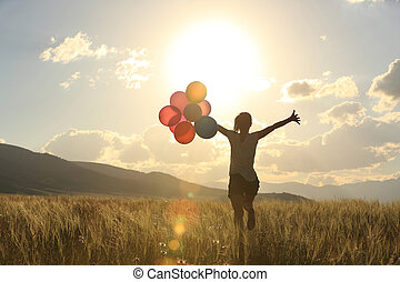 cheering young woman on grassland with colored balloons