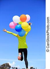 cheering young woman running on mountain peak