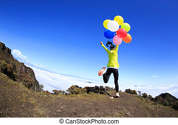 cheering young woman running on mountain peak with colorful balloons