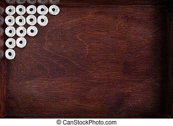 Cheerios lined as angle into dark wood box