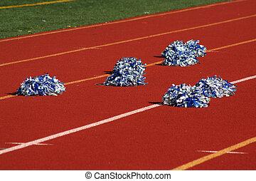 Cheerleader pom poms near a football field