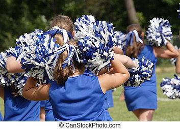 Teen Youth Cheerleaders cheering at football game.