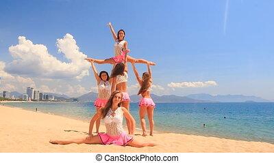 cheerleaders dance perform high split swing stunt on beach
