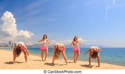 cheerleaders dance show varied poses on beach against sea
