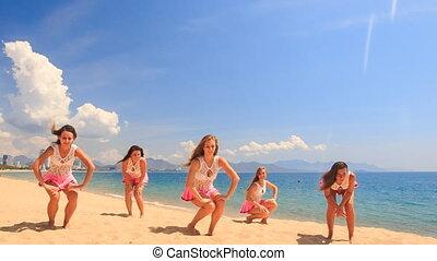 cheerleaders dance squat show poses on beach against sea