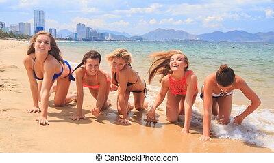 cheerleaders in bikinis crawl in line along sand beach smile