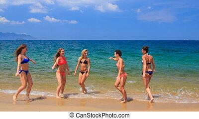 cheerleaders in colourful bikinis jump gambol in water
