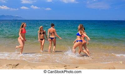 cheerleaders in colourful bikinis jump wave hands in water