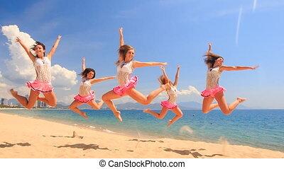 cheerleaders in uniform dance in jump stunt on beach against sea