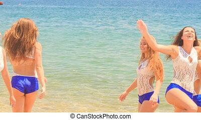 cheerleaders in uniform jump gambol in shallow water against sea
