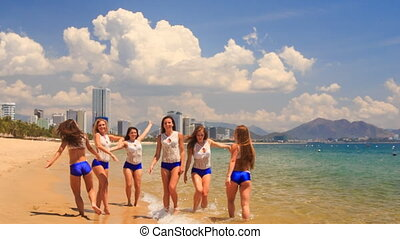 cheerleaders in uniform jump gambol wave hands in shallow water