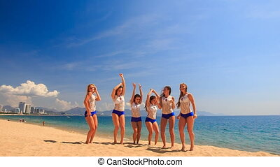 cheerleaders in uniform perform Toe Touch Basket Toss on beach
