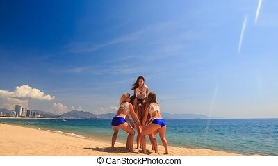 cheerleaders in uniform perform Toe Touch Toss on beach