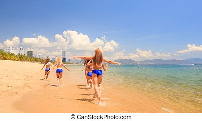 cheerleaders in uniform run gambol about shallow water on beach