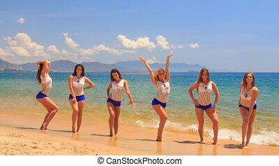 cheerleaders in uniform step out of water stand in line on beach