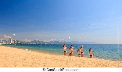 cheerleaders in white blue do stunt Swedish falls on beach