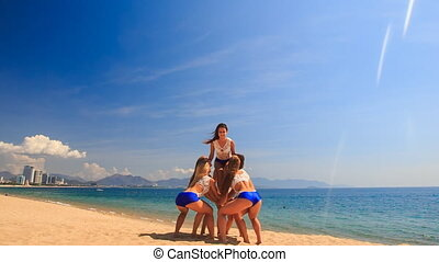 cheerleaders in white blue perform Back Tuck Basket Toss on sand