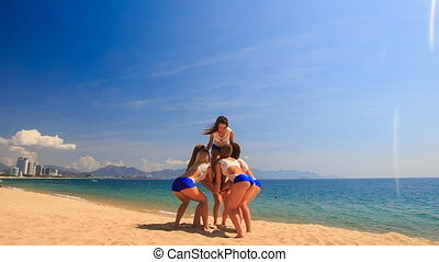 cheerleaders in white blue perform Basket Toss on beach