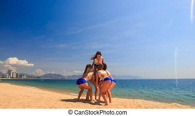 cheerleaders in white blue perform Basket Toss on beach