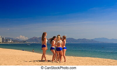 cheerleaders in white blue perform half stunt pyramid on beach