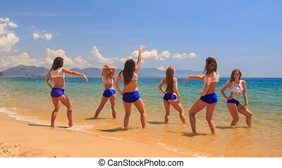 cheerleaders in white blue run out of water dance on beach