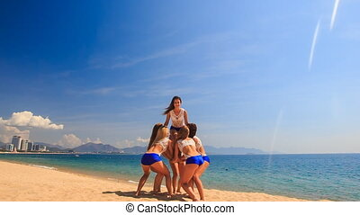 cheerleaders in white blue show Basket Toss on beach
