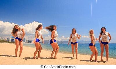 cheerleaders in white blue show Heel Stretch Pyramid on beach