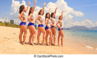 cheerleaders in white blue stand in line run into water on beach