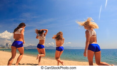 cheerleaders run out perform Basket Toss on beach