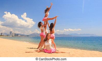 cheerleaders show high split swing stunt on beach against sea