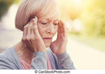 Cheerless elderly woman holding her temples