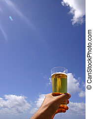 Hand with beer and blue sky; celebration