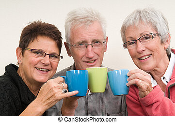 Cheers - Three seniors holding a cup of coffee.