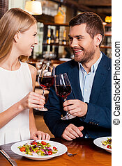 Cheers to us! Beautiful young loving couple toasting with red wine and smiling while sitting at the restaurant together