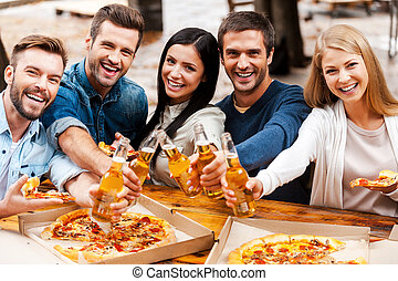 Cheers to you! Group of happy young people bonding to each...